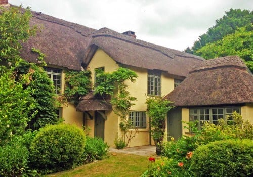 Pretty thatched cottage with roses and shrubs