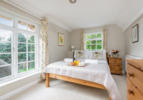 New Forest cottage bedroom with side garden view and breakfast tray