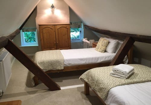 Sloped ceilings with traditional wood beams and comfy single beds quirky bedroom in 18th century Beck Cottage