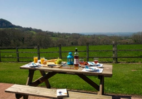 Picnic table laid for lunch with glorious views across the fields