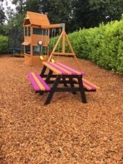 Colourful quirky bench in the play area at Criddlestyle Cottage perfect for alfresco dining for the children or the whole family