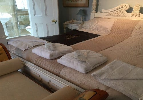 Robes and towels on the bed in this master suite
