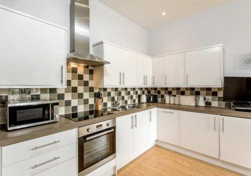 Bright white fully stocked kitchen with monochrome tiles