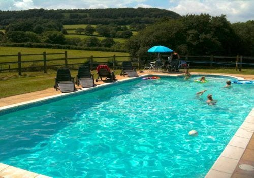 Swimming pool with kids playing and rolling fields behind