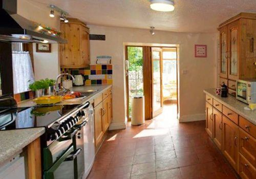 Large farmhouse kitchen with bright colouful tiles and door leading to conservatory