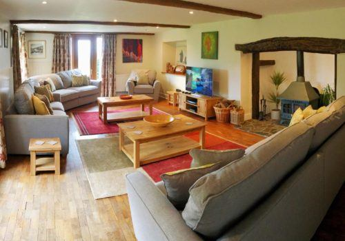 Spacious lounge with inglenook fireplace and beamed ceiling