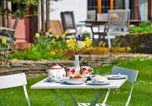 Bistro table with afternoon tea and scones in the sunshine