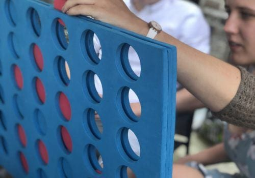 Guest playing Connect 4 in The Quays garden