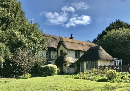 Beautiful thatched cottage with sun and blue skies