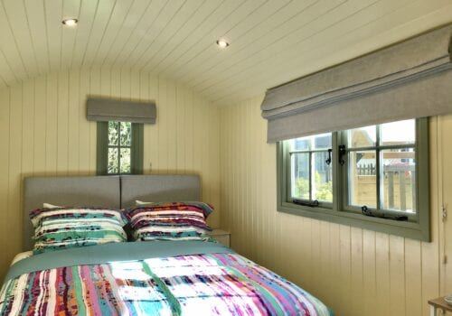 Interior of the Shepherds hut with brightly coloured bedspread